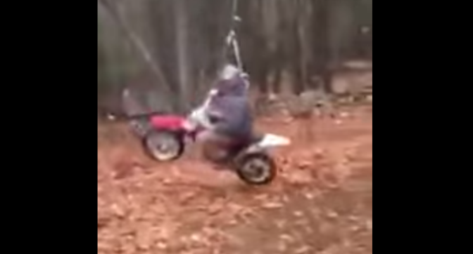 Dad rides a swinging dirt bike attached to a rope