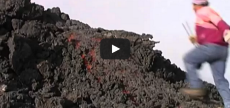 Lava run: man runs over glowing lava flow on volcano Etna