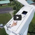 Drone catches guy secretly sunbathing on top of wind turbine