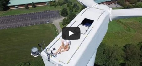 Drone catches guy secretly sunbathing on top of wind turbine